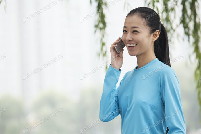 Young woman talking on cell phone in the park