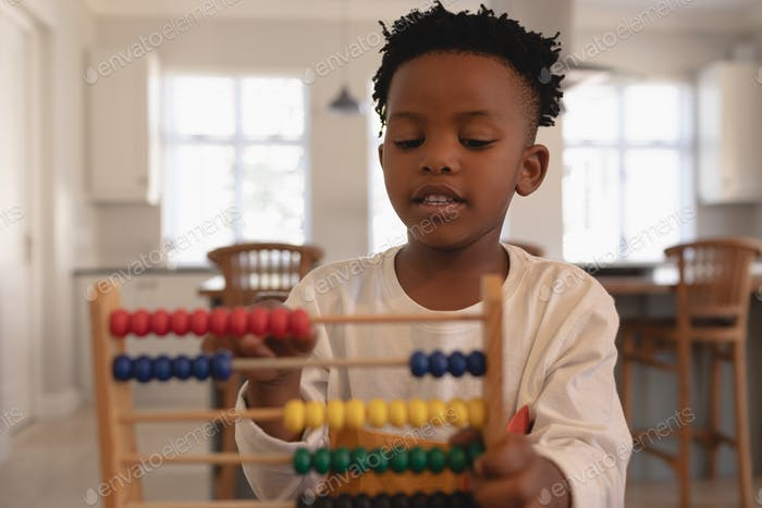 Front view of cute African American boy learning mathematics with abacus in a comfortable home