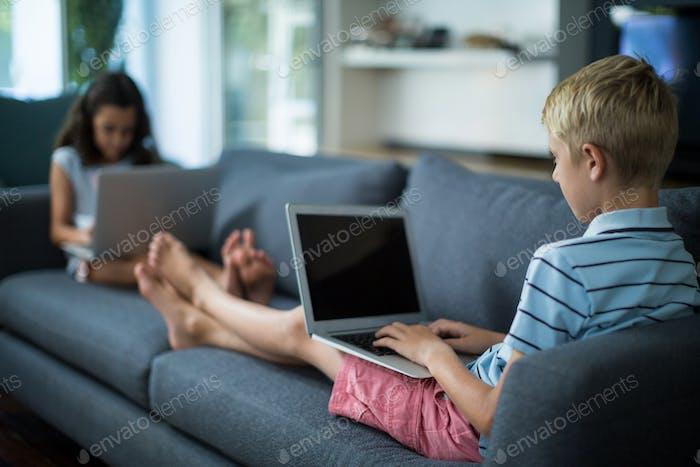 Siblings using laptop in living room