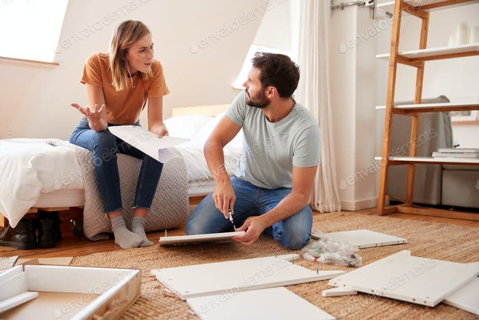 Couple Having Argument Whilst Putting Together Self Assembly Furniture