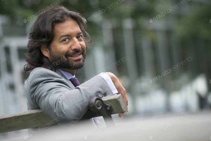Мужчина в деловом костюме с полной бородой и вьющимися волосами.