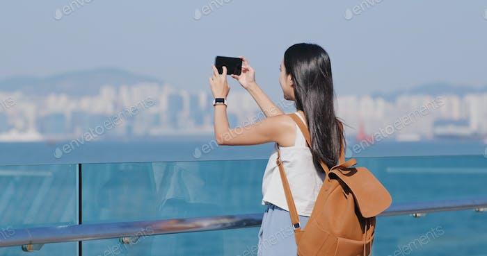 Frau nehmen Foto auf Handy in Hong Kong