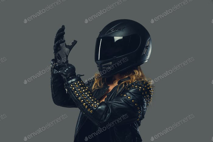 Female in leather clothes, moto gloves and safety helmet.
