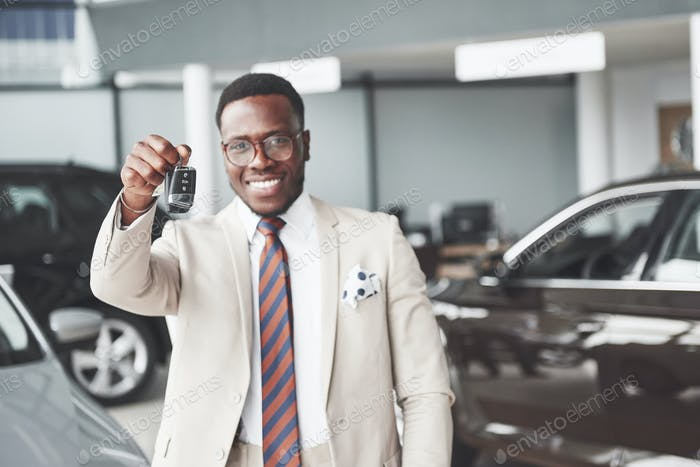 The young attractive black businessman buys a new car, he holds the keys in his hand. Dreams Come