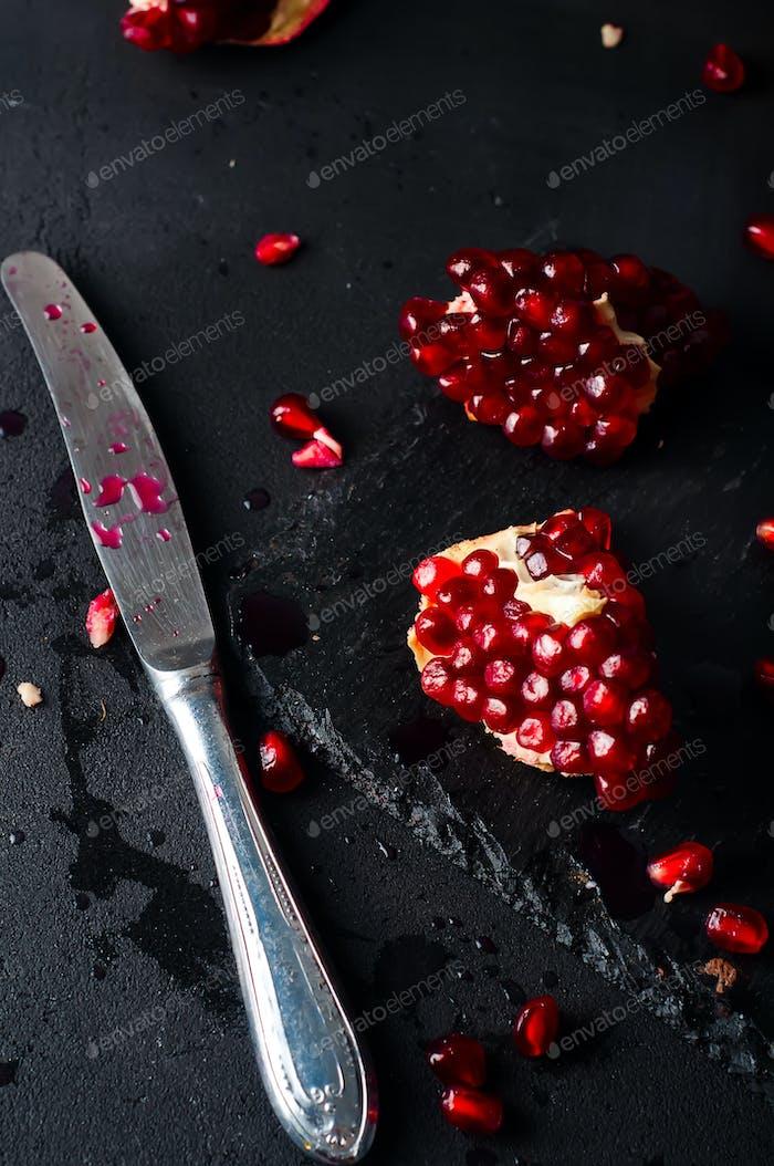 Granatäpfel und Granatapfelkerne auf dunklem Hintergrund