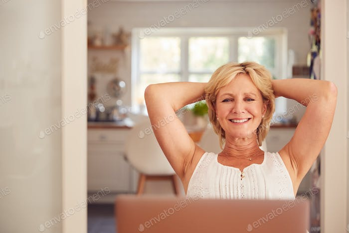 Retired Woman At Home In Kitchen Happy With Sense Of Achievement At End Of Day Working On Laptop