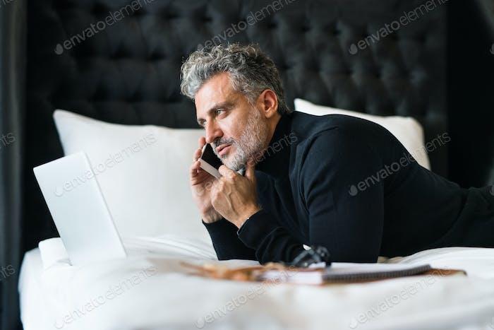 Reife Geschäftsmann mit Smartphone in einem Hotelzimmer.