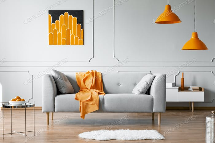 Orange blanket on grey couch in bright flat interior with lamps and poster on the wall. Real photo