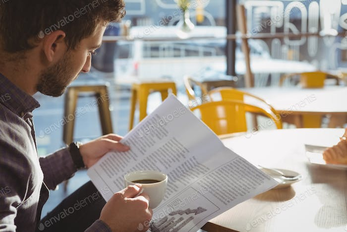 Businessman having coffee while reading newspaper