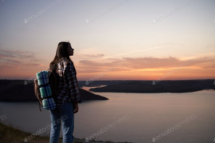 Attractive woman hiking during amazing sunset