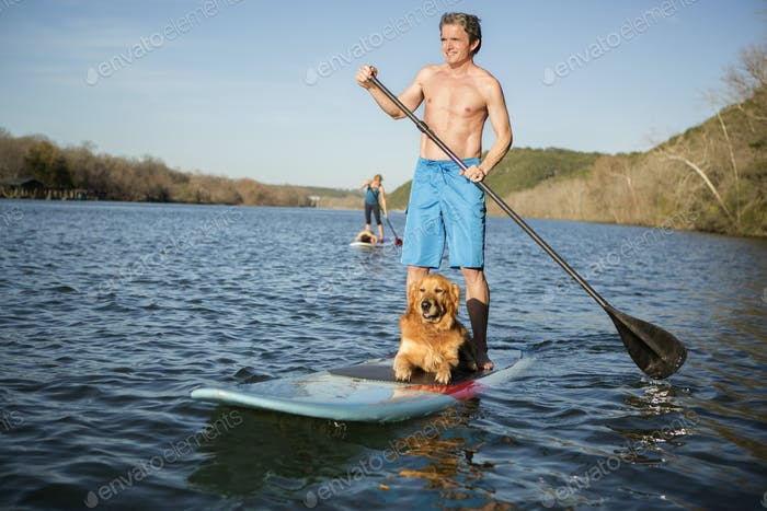 A man standing on a paddleboard with a dog.
