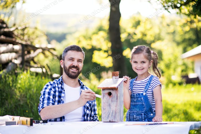 Father with a small daughter outside, painting wooden birdhouse.