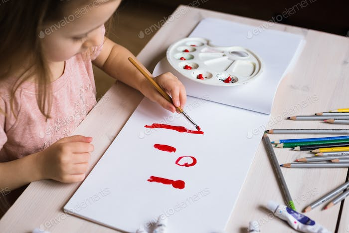 Cute little girl painting picture on home interior background Foto ...