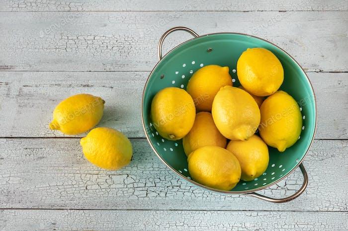 Свежие лимоны в дуршлаге