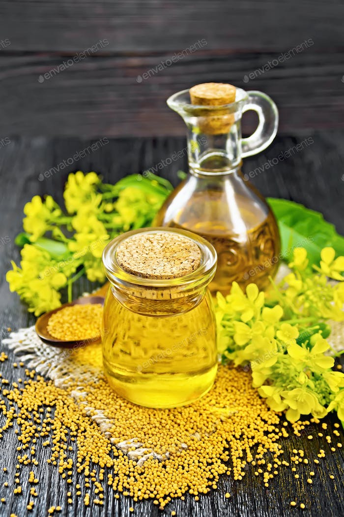 Oil mustard in jar and decanter with flower on dark wooden board