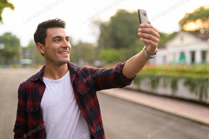 Happy young handsome Hispanic hipster man taking selfie at the park