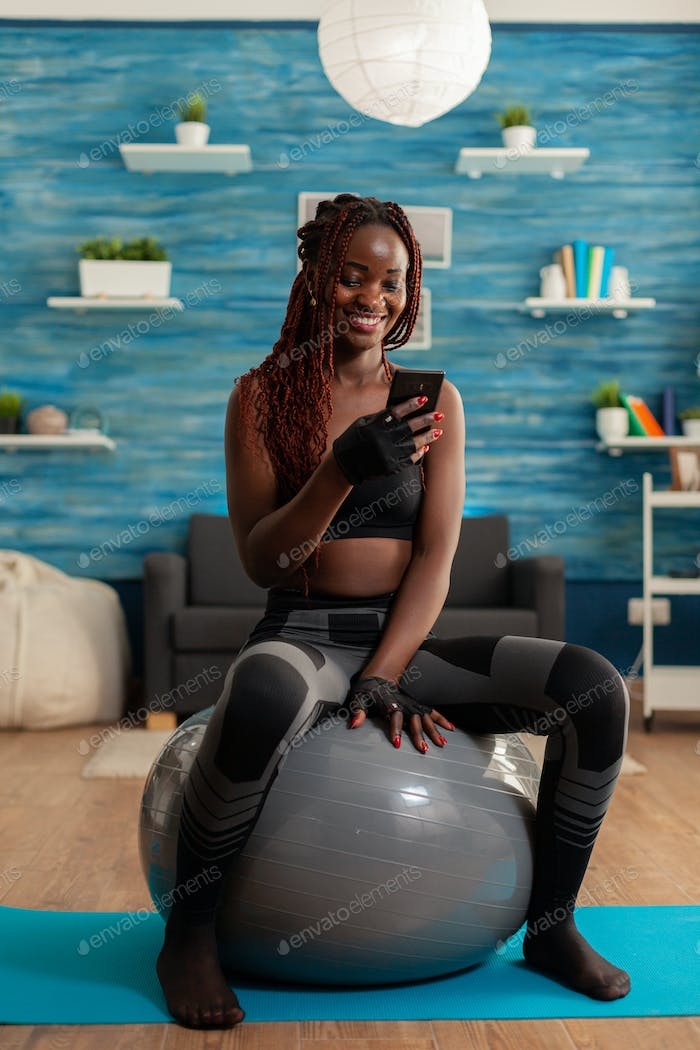 Sporty athletic black woman relaxing on stability ball