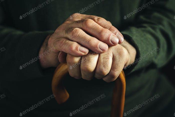 Dedos artríticos retorcidos de un anciano