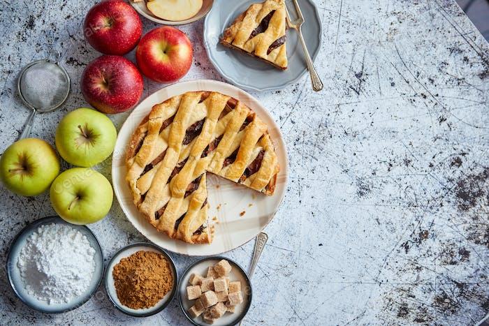 Köstlicher Apfelkuchen mit frischem Obst, braunem und Puderzucker