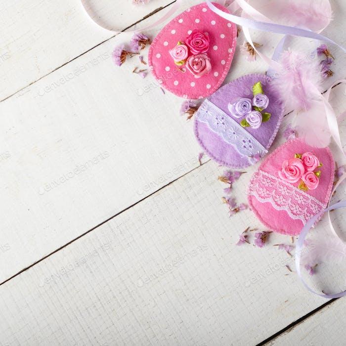 Handgefertigte Patchwork rosa und lila Filz Ostereier auf weißem Holz