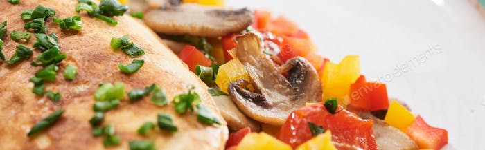Вкусный омлет с овощами на тарелке