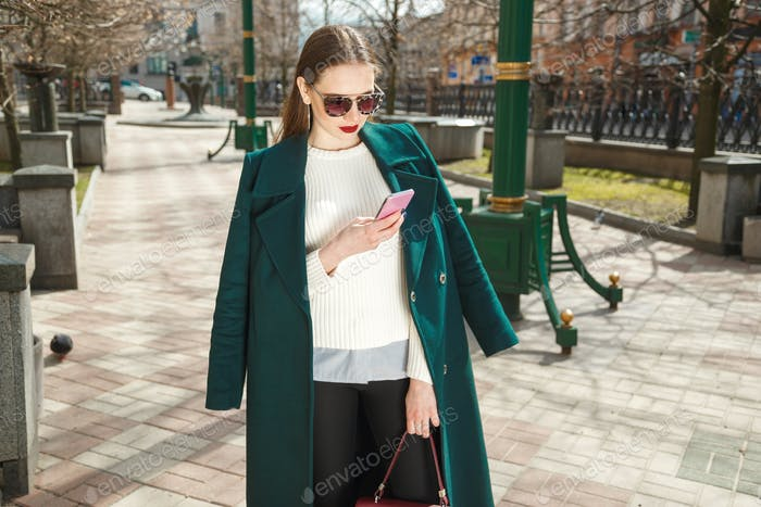 Young brunette woman wearing casual coat writes sms online with smartphone chatting at street