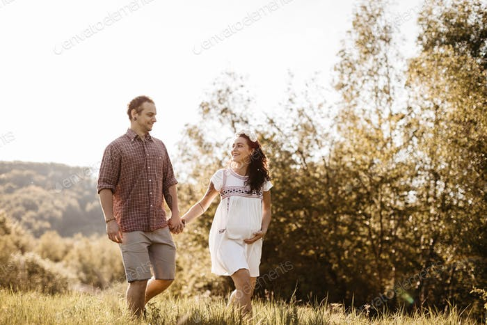 Cheerful expecting couple walking in the nature
