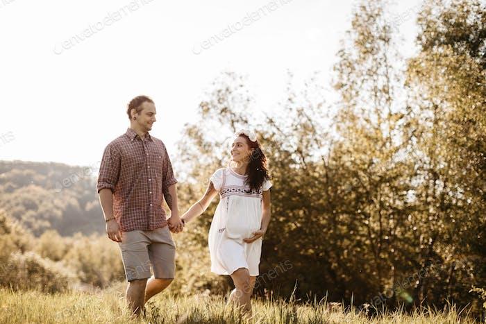 Fröhlich erwartet Paar zu Fuß in der Natur