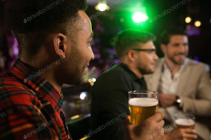 Man having beer with his friends in a pub