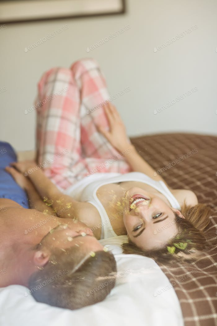 Cute couple lying on bed at home in the bedroom