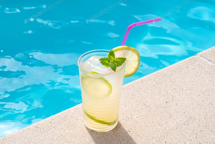 Fresh drinking glass with straw on a swimming poll border