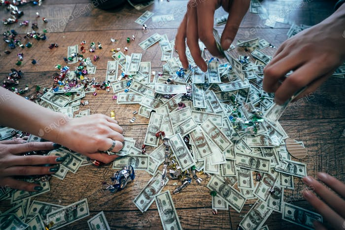 Several pairs of hands pick up dollar bills from the floor