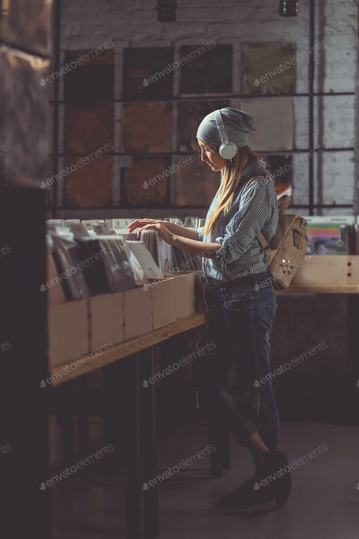 Young attractive girl browsing records indoors