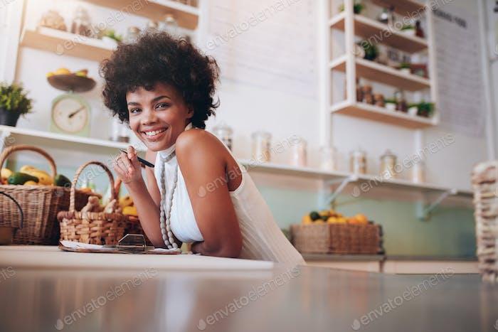 Lächelnde junge Frau arbeitet in einer Saftbar