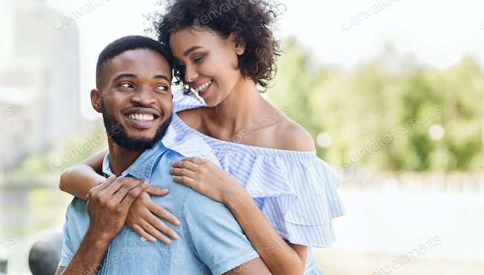 Loving african-american couple in love hugging in park