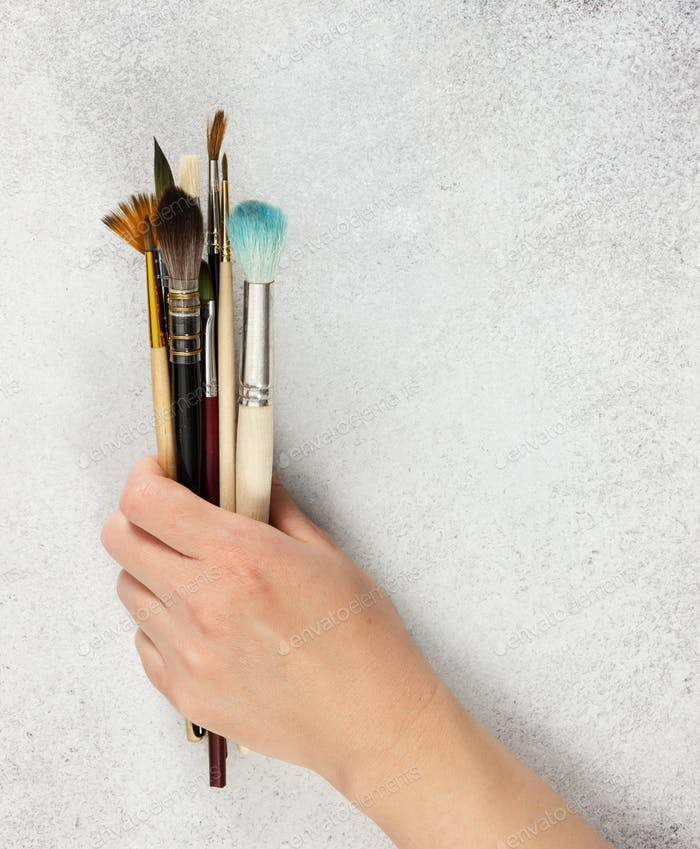 Artistic brushes in a female hand