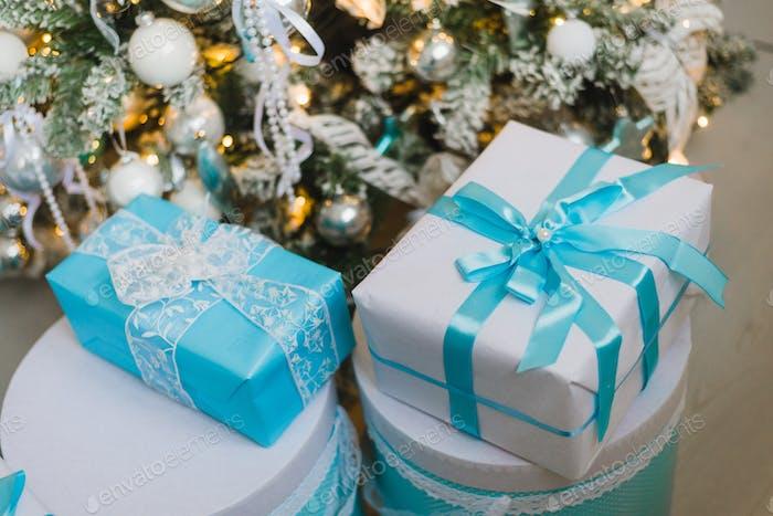 Weihnachtsgeschenk-Boxen mit blauer Schleife und Bokeh Lichter auf Holzoberfläche