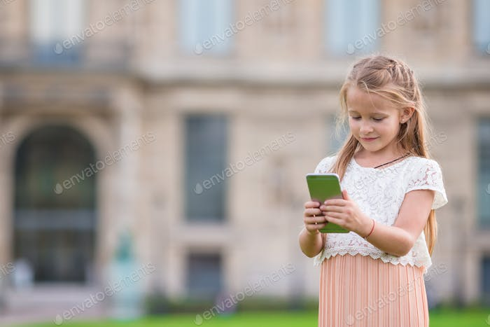 Adorable toddler girl with phone in Paris during summer vacation