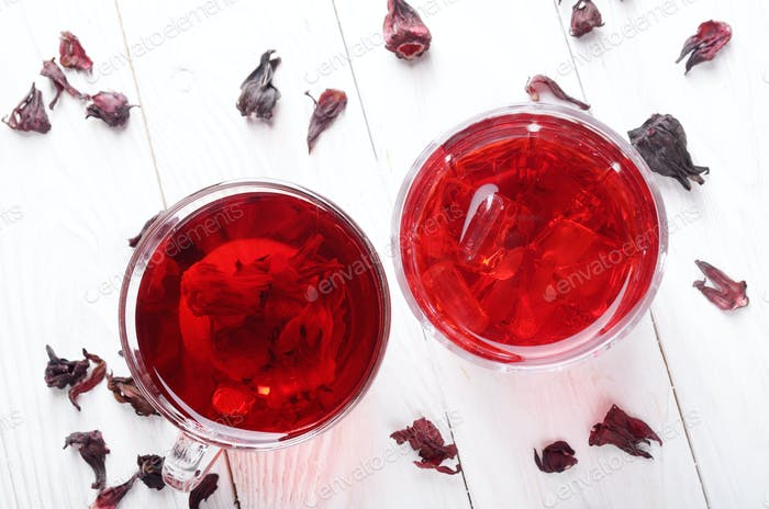 Top view at two tea cups with ice and dry hibiscus petals on whi