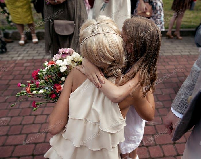 kleines Mädchen umarmt Braut