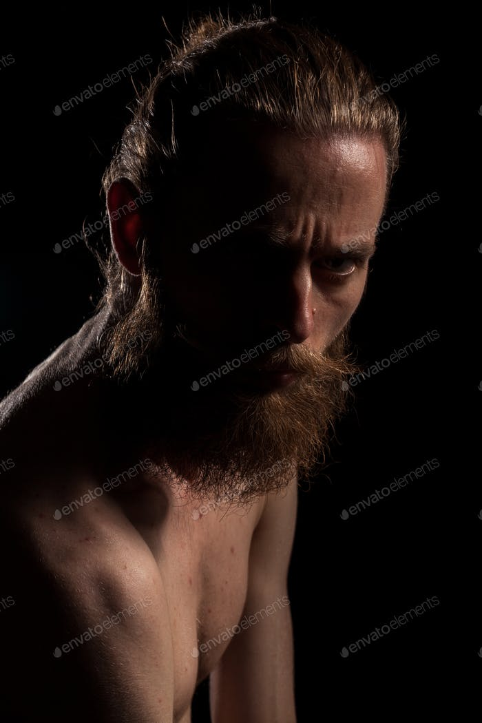 Portrait of bearded guy on black background