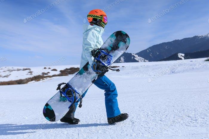 Snowboarder walking on alpine mountain slope