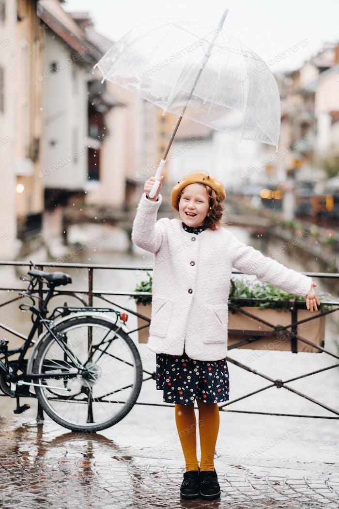 fröhlich schönes Mädchen in einem Mantel mit einem transparenten Regenschirm in Annecy. Frankreich. Das Mädchen Fröhlich