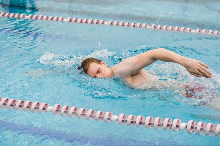 man swims using the crawl stroke in indoor pool