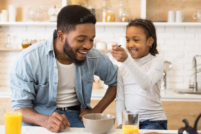 Adorable afro girl feeding her dad cereals