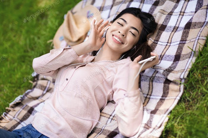 Relaxing Music. Asian Woman Listening Favorite Songs, Lying On Plaid In Park