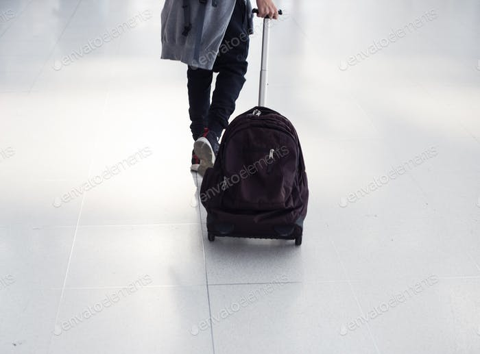 Young caucasian man travel with luggage in the airport