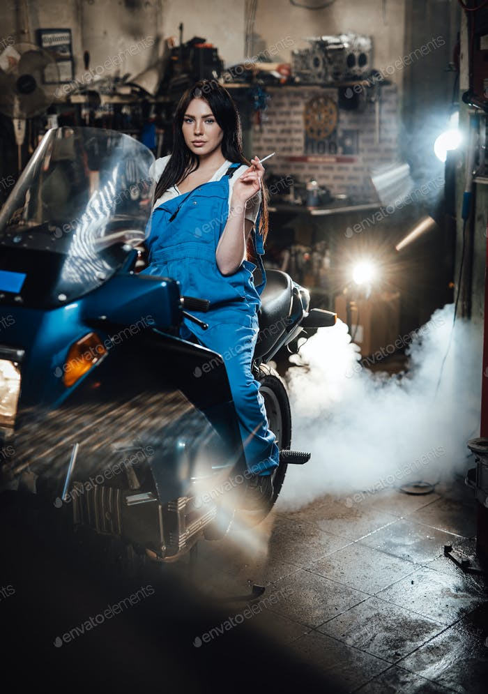 Beautiful brunette female mechanic smoking a cigarette while sitting on sportbike in garage