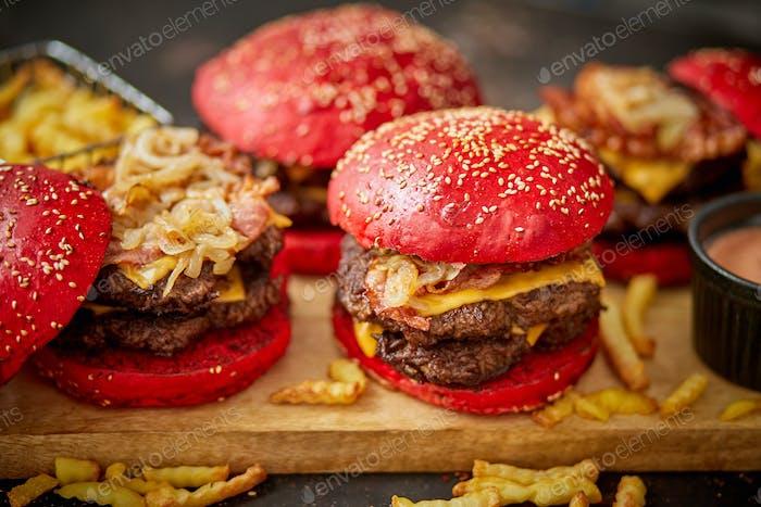Eine Reihe von roten Brötchen hausgemachte leckere Burger Rindfleisch, Speck, Käse, gegrillte Zwiebel auf einem dunklen rostigen