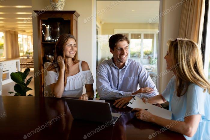 Pareja joven discutiendo con un asesor financiero en casa